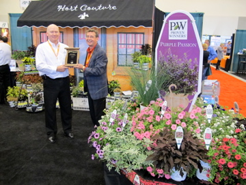 4309_chris_johnston_of_jvk_accepts_a_best_booth_award_from_trade_fair_committee_member_wayne_brown