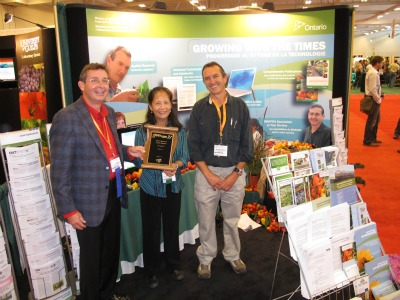 4398_trade_fair_committee_member_wayne_brown_presents_the_a_technology_display_award_to_omafra_representatives_gillian_ferguson